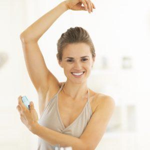 happy young woman applying deodorant on underarm